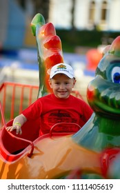 Happy smilling boy driving car toy at an amusement park