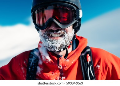 happy snowboarder is standing in the red suit on the snow powder hill and smiling