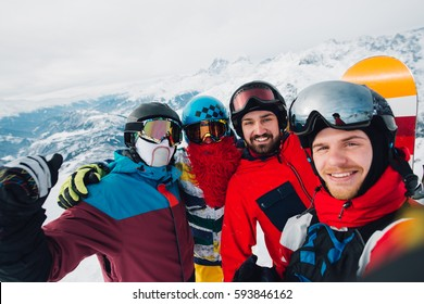 Happy snowborders is standing and making selfie on the mountain