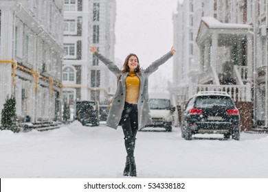 Happy snowing winter time in big city of pretty girl enjoying snowfall on street. True positive emotions, holding hands above, smiling, love your life, waiting for christmas, winter holidays
