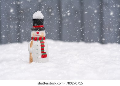 Happy snowman standing in christmas landscape with copy-space and snow background