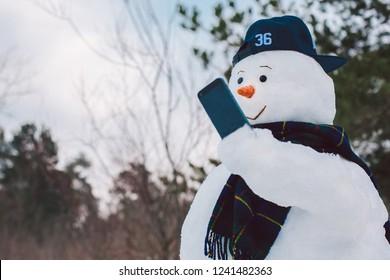 Happy snowman using smart phone  at park