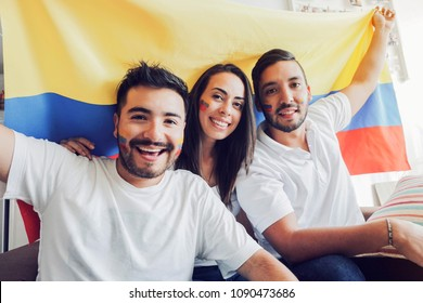 Happy soccer fans holding a colombian flag and looking at camera
