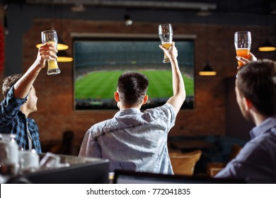 Happy soccer fans. Three friends watching a game at the pub.