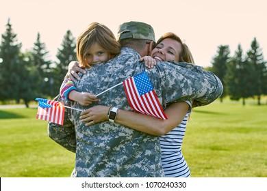 Glücklicher Soldat mit seiner Familie an dem sonnigen Tag. Nahaufnahme von Umarmungen, Wiedervereinigung im Parkrasen.