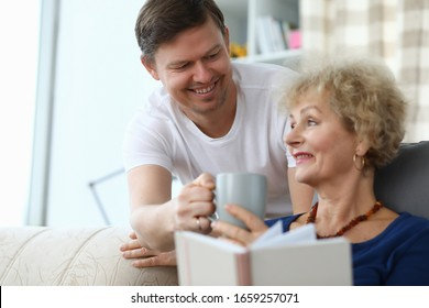 Happy son brought cup tea for an elderly mother. Son cares for an elderly mother at home. An adult son decided to stay with his mother alone. Have fun with your parents. Good family relationships
