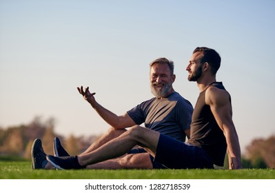 The happy son and father sitting on the grass