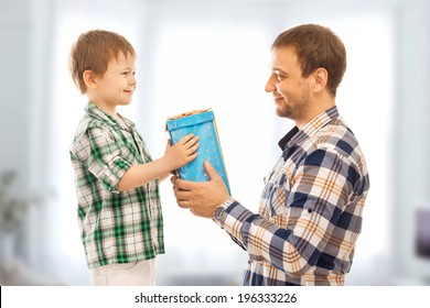 Happy son gives his father gift. Fathers day, family holiday, vacation.
