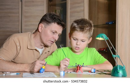 Happy son and his father are making aircraft model. Hobby and family concept. Creating the model plane.