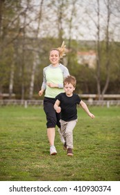 Happy son and mother doing exercises in the summer park. on the stadium, outdoor. Sport activities with children. Healthy lifestyle. Fitness exercises. Young mother and son running together