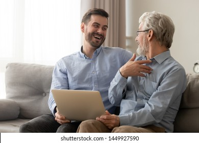Happy son and old father having fun at home, using computer together, discussing funny news or movie, mature senior dad and millennial man holding laptop, sitting on couch, enjoying weekend