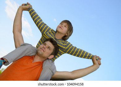 Happy son on the shoulders of the father. On the background of blue sky