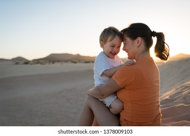 Happy son smilling and hugging with his mother on sand dune in desert during sunset