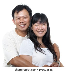 Happy southeast Asian mature couple hugging and smiling, isolated on white background.