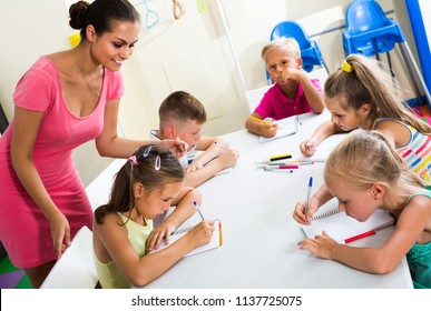 happy spanish  children making writing exercises with help of teacher in class