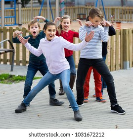 happy spanish  children showing different figures during game in playground outdoors