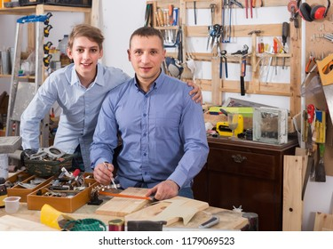happy spanish family of two posing at workplace in garage and smiling