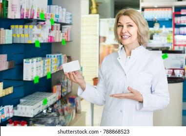 happy spanish female pharmacist   posing in drugstore