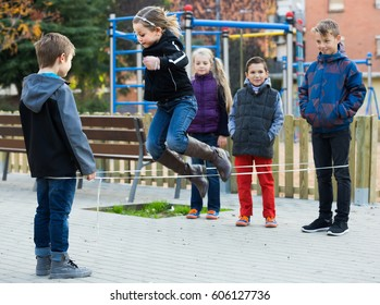 happy spanish kids skipping on chinese jumping elastic rope in yard