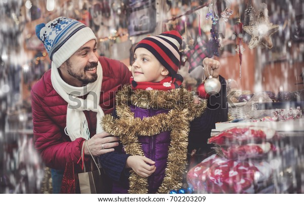 happy spanish little girl with dad buying decorations for Xmas. Focus on girl