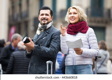 happy spanish mature couple with suitcases, camera and map outdoors