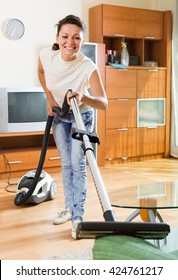 Happy spanish middle-aged woman hoovering apartment