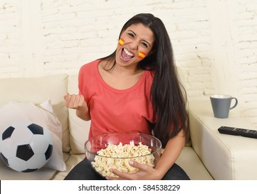 happy Spanish woman football fan at home sofa couch watching excited television soccer game eating popcorn cheering and supporting  Spain celebrating victory or goal with flag face painted