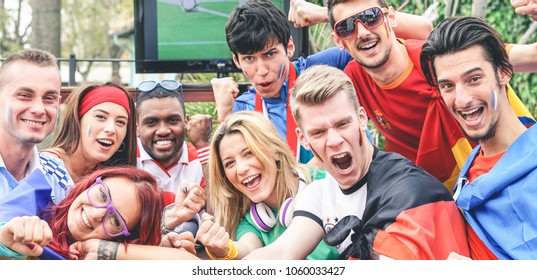 Happy sport fans having fun during football world game - Young supporters at pub outdoor watching soccer match - Friendship, sport , bonding and youth concept - Main focus on right bottom guys