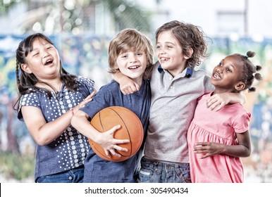 Happy sport school scene. Multi ethnic classroom playing basketball.
