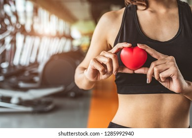 Happy sport woman holding red heart in fitness gym club. Medical cardio heart strength training lifestyle. Pretty female sport girl workout exercise. Cardiac healthy and well-being. Massage ball in ha