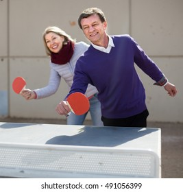 Happy sports mature man and a woman playing table tennis