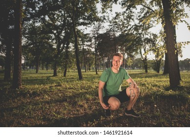 Happy sportsman relaxing after training in the forest