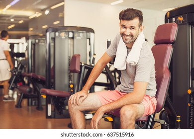 Happy Sportsman with Towel on Exercise Machine