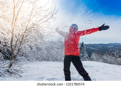 Happy sportsman wearing red jacket throwing snow in the air