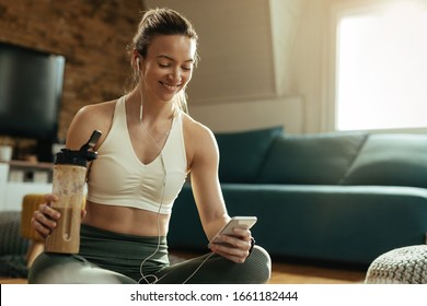 Happy sportswoman using smart phone while drinking protein shake after a workout at home.