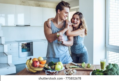 Happy sporty couple is preparing healthy food on light kitchen. Healthy food concept.