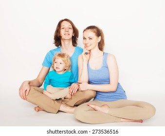 Happy sporty family - mother, father and little son posing over white background
