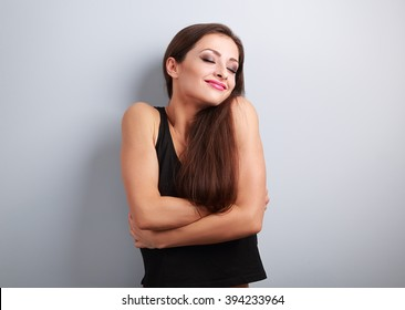 Happy sporty fit woman hugging herself with natural emotional enjoying face. Love concept of yourself