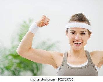 Happy sporty girl showing biceps