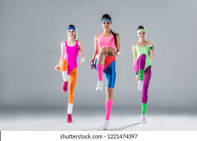 happy sporty girls in bodysuits training at aerobics workout on grey