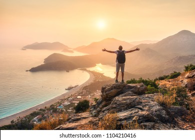 Happy sporty man with backpack and raised up arms standing and on the rock and looking at the seashore and mountains at sunset in summer. Man, sea, mountain ridges and orange sky. Oludeniz, Turkey