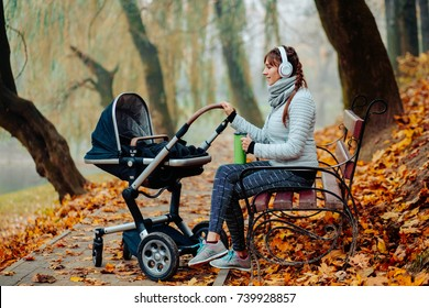 Happy sporty mother in headphones listening music and drinking rea from thermos cup with baby in buggy sitting on bench in autumn park. Full body