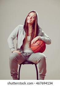 Happy sporty teenager girl wearing hooded sweatshirt holding basketball. Teen sport.