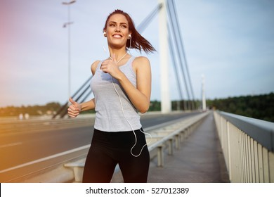 Happy sporty woman jogging outdoors