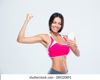 Happy sporty woman making selfie photo on smartphone over gray background