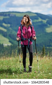 Happy sporty woman tourist with backpack and trekking sticks, wearing sports wear, standing on the top of a hill, smiling, looking away, resting after hiking, enjoying summer day in the mountains
