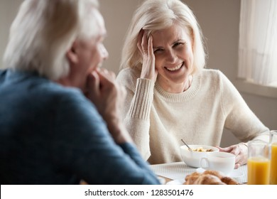 Happy spouses old wife husband laughing joking sitting together at dinner table during healthy breakfast. Family eating food drinking fresh orange juice talking in the morning, closeup focus on woman
