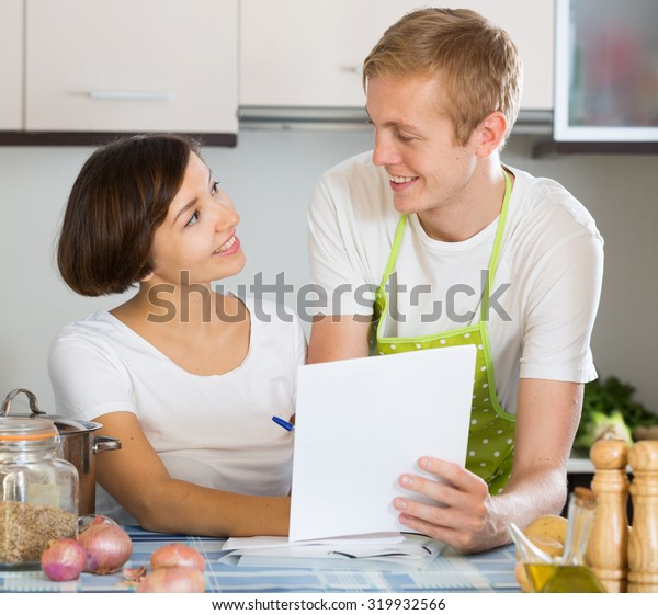 Happy spouses signing documents and smiling at home