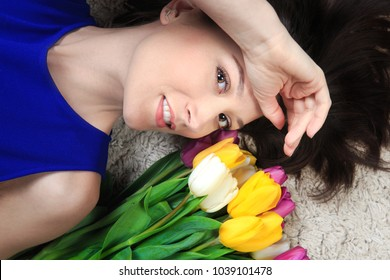 Happy spring woman. Brunette model with tulips on soft carpet view from above. Smiling girl with clean light skin.