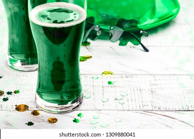 Happy St Patricks Day background with leprechaun hat, shamrock shaped glasses and green ale. Greeting card. Copy space